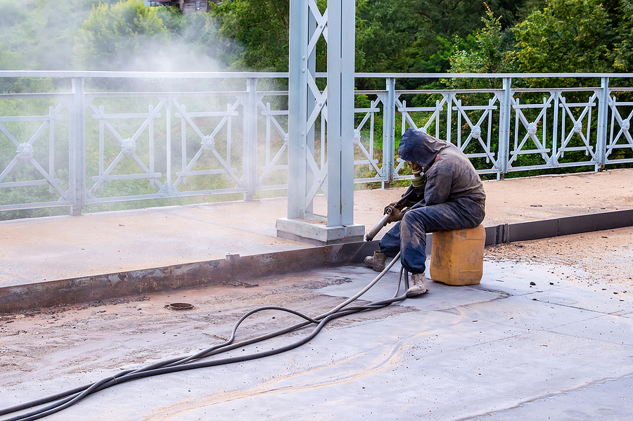 Worker while doing concrete sandblasting